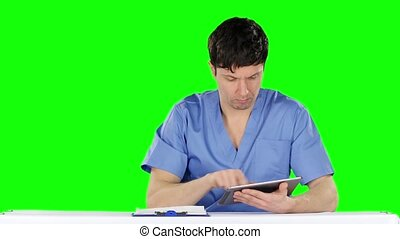 Young doctor uses a tablet and shows thumb down. Green...