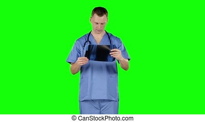 Doctor analyzing x-ray. Green screen - Doctor analyzing...