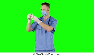 Male doctor preparing a syringe for injection Green screen -...