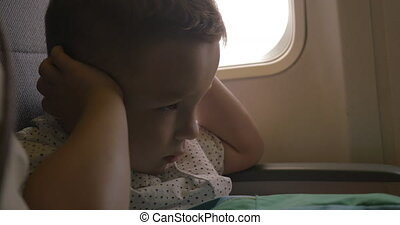 Kid shutting ears at the airplane - Nervous little child...