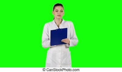 Nurse or young doctor writing on medical file clipboard. Green screen