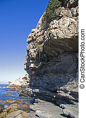 Rocky coastline of Hermanus South Africa with blue skies