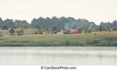 Smoke from fire in camp with tents and car on river bank -...