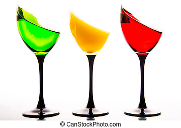 three wine glasses filled with the  colors of traffic lights