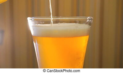 Jet of light beer fills in a beer glass on the table