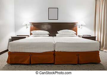 White twin bed with picture frame in hotel room