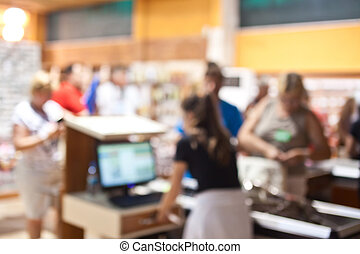 People pay for purchases at the checkout. Blurred.