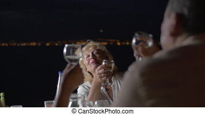 People clinking glasses of wine while sitting at table