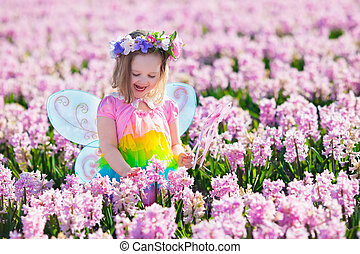 Little girl in fairy costume playing in flower field -...