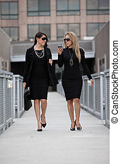 Two attractive hispanic businesswomen outdoor in their...