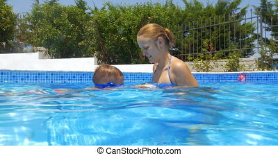 Woman, Boy and Ball in Swimming Pool - Woman and little boy...