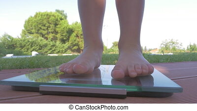 Child on bathroom scales outdoor - Close-up shot of little...