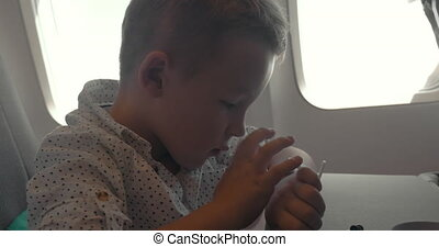 Child using smart watch during air travel - Little boy using...