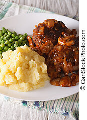 Salisbury steak with mashed potatoes and green peas close-up...