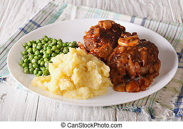 Salisbury steak with potatoes and green peas close-up on a...