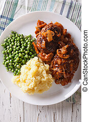 Salisbury steak with potatoes and green peas close-up...