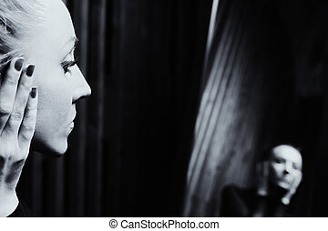 Portrait of a young sad woman looking in the mirror