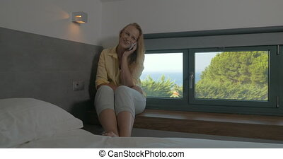 Young excited woman talking on mobile in hotel - Young...