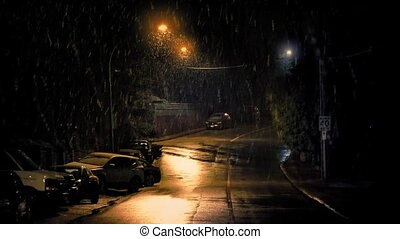 Snow Falling On Road In The City - Night scene of road near...