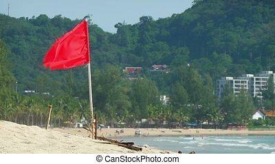 Red Warning Flag over a Tourist Beach in Southeast Asia -...