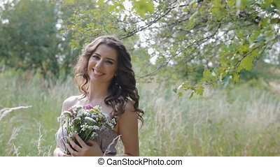 Young pretty woman with bouquet of wildflowers - Young...