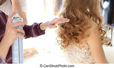 Close-up of hairdresser doing beautiful wedding hairstyle.
