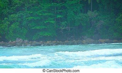 Small waves break along a rocky coastline - Small, gentle...