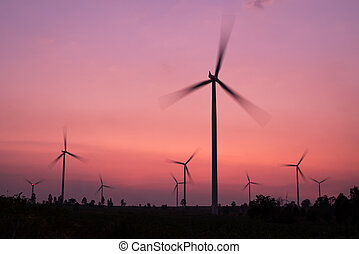 wind turbines spinning at twilight - silhouette of wind...