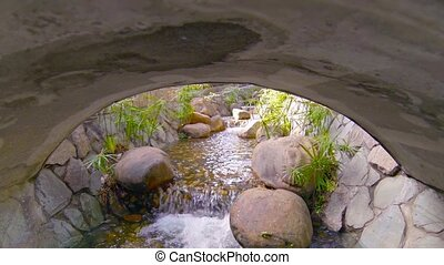 """Decorative Stream Flows around Boulders and Under Bridge,..."