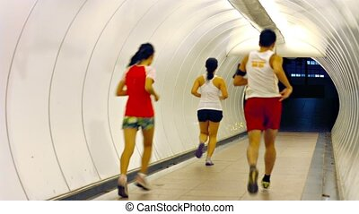 Joggers Running through a Brightly Lit Pedestrian Tunnel -...