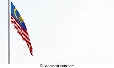 Malaysian National Flag Waving in a Breeze against an...