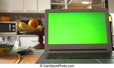 Laptop with green screen on the kitchen table - Laptop on...