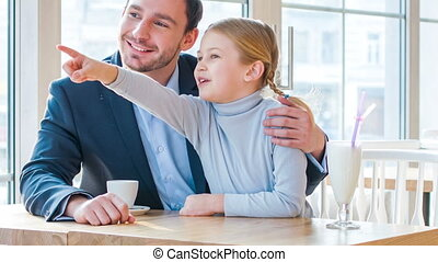 Positive father and his daughter sitting in the cafe - Look...