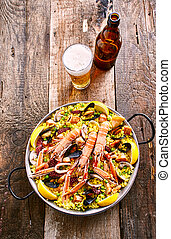 Spanish Seafood Paella Dish with Refreshing Beer - High...