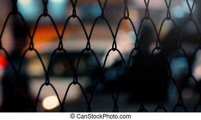 City Nightlife Thru Fence Abstract - Vibrant city scene with...