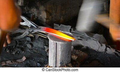 Men Pounding Red Hot Steel in a Traditional Blacksmith Shop....