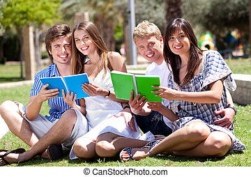 Smiling young couple holding books posing to camera in the...