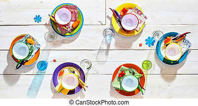 Colorful picnic table place settings with empty multicolored...