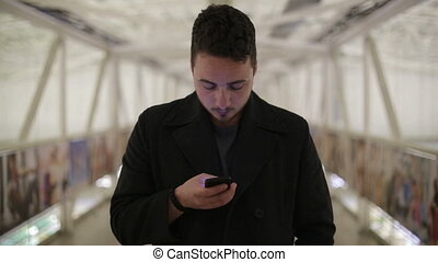 Young man with a smartphone on the covered bridge Day