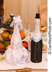 Champagne bottles decorated as a bride and groom