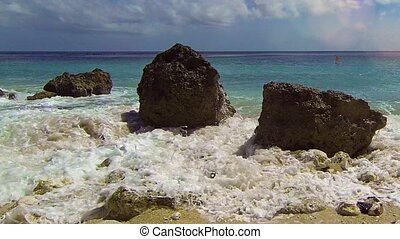 Gentle Waves Wash over Boulders on a Tropical Beach...