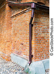 drainpipe on red brick weathered wall
