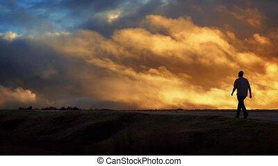Man Walks Across Horizon At Sunset - Male figure walks...