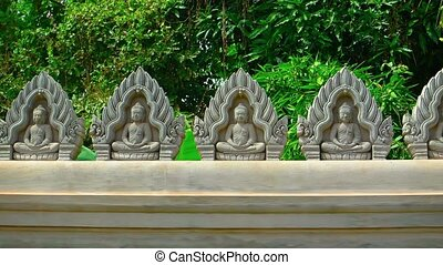 """Buddhist Sculptures atop a Temple Wall in Siem Reap,..."