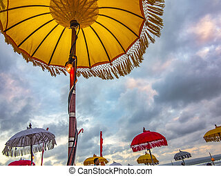 Traditional ceremonial umbrellas and flags on beach at...