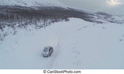Aerial view of car driving on snowy mountain road - Flying...