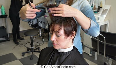 Stylist makes a short cut - The stylist cuts the hair of a...