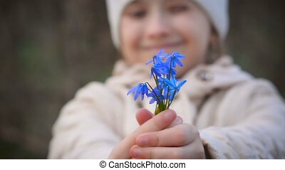 Girl holding a blue snowdrops - Beautiful girl holding a...