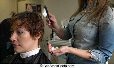 Stylist to put foam on the hair - Stylist with a comb to put...