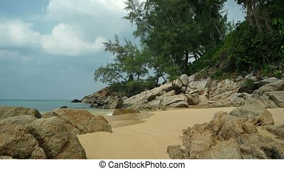 Gentle Waves Splash against Boulders on a Tropical Beach....